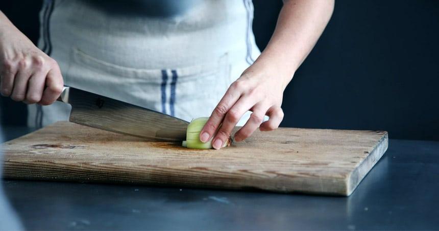 Chef Knife - Chef cutting onion on cutting board.