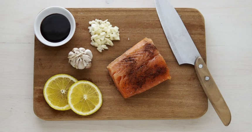 Meat cutting board with lemon, soy sauce and fish.